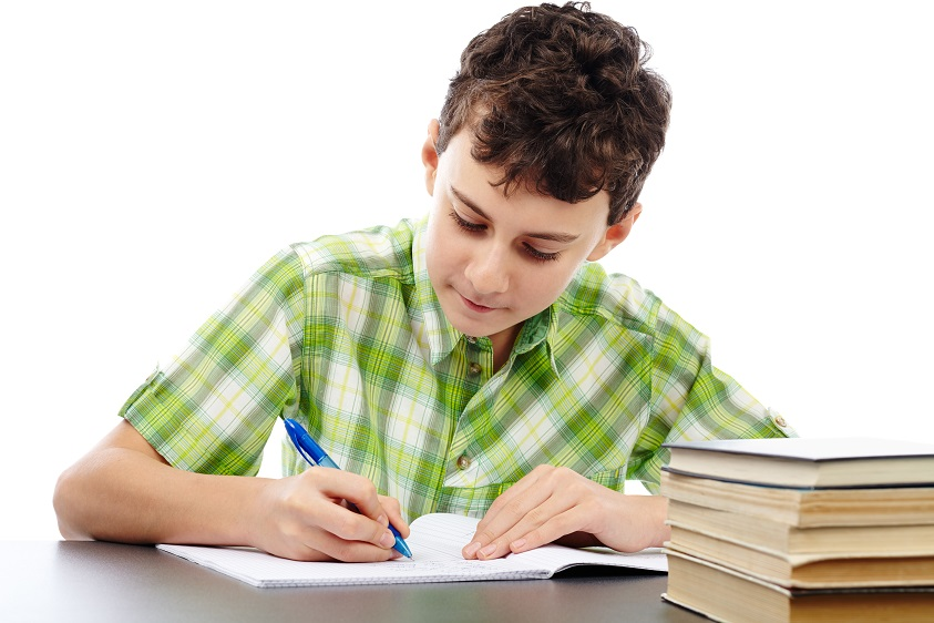 Caucasian student boy at his desk writing for homework