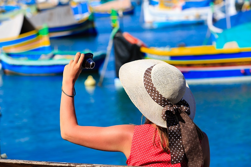 tourist making photo of colorful traditional boats in Marsaxlokk, Malta