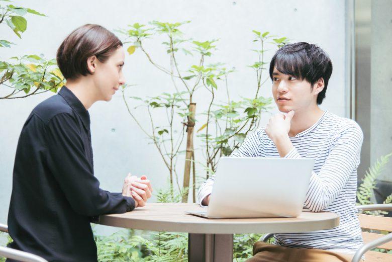 屋外のテラスでミーティングをする外国人の男女(国際化イメージ)