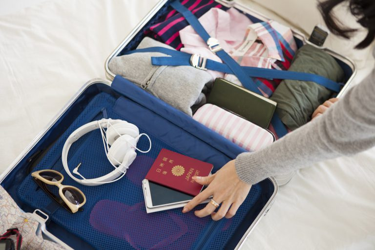 Women are packing a suitcase on the bed