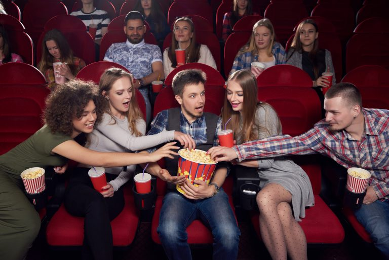 International group of women and men spending time at cinema, pulling hands to popcorn of one shocked boy in center. Greed, angry and surprised man holding big bucket with tasty popcorn.