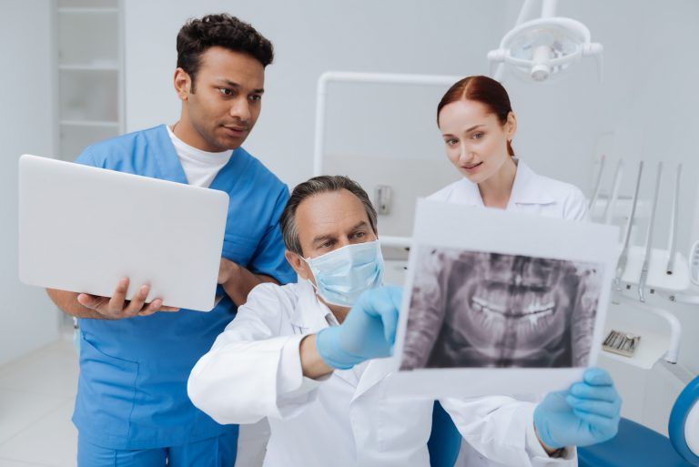 Look attentively. Competent dentist wearing mask on his face and holding picture of jaw while sitting between two assistants