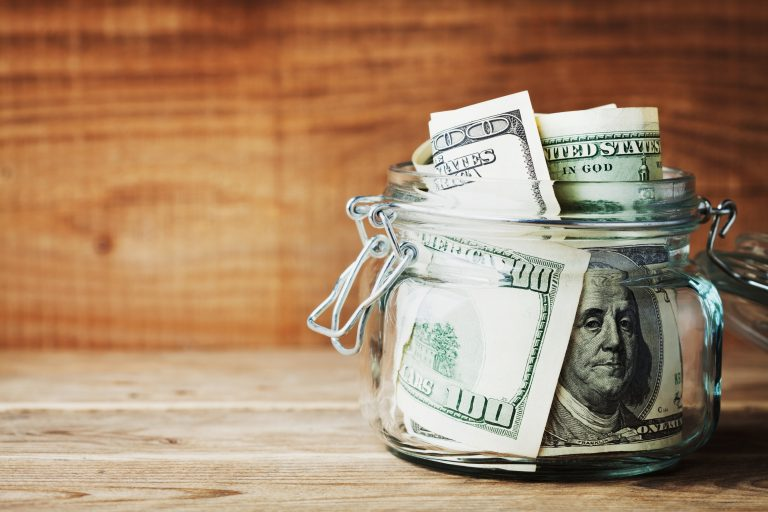 Dollar bills in glass jar on wooden background. Saving money concept.