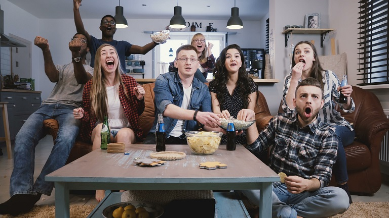 Friends watch sports on TV, cheer and celebrate. Happy diverse supporters fans sit on couch, popcorn snacks and drinks. 4K Emotion and expression. Multicultural people excited and joyful. Bonding time