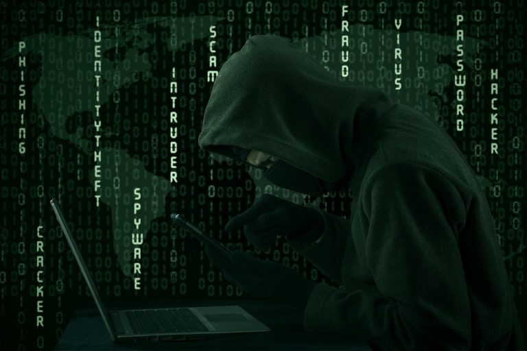 Hacker looking for password and user information using digital tablet and laptop computer